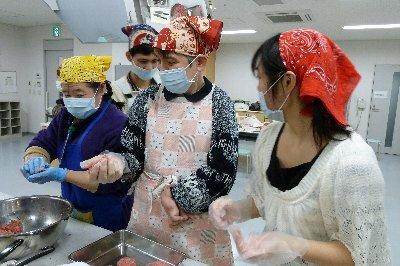 片手でハンバーグを作る参加者とそれをサポートする学生ボランティア