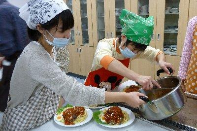 ハンドーグとスパゲティーにトマトソースをかける参加者とそれをサポートする学生ボランティア
