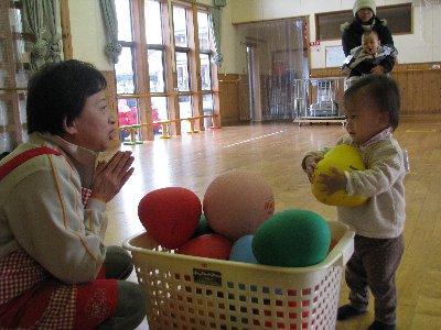 ボール遊びをしながら乳児と見つめ合う児童厚生員