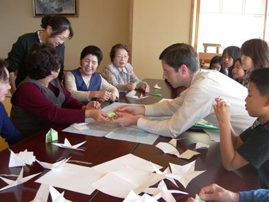 国際交流員と折り紙を楽しむお年寄りと子どもたち
